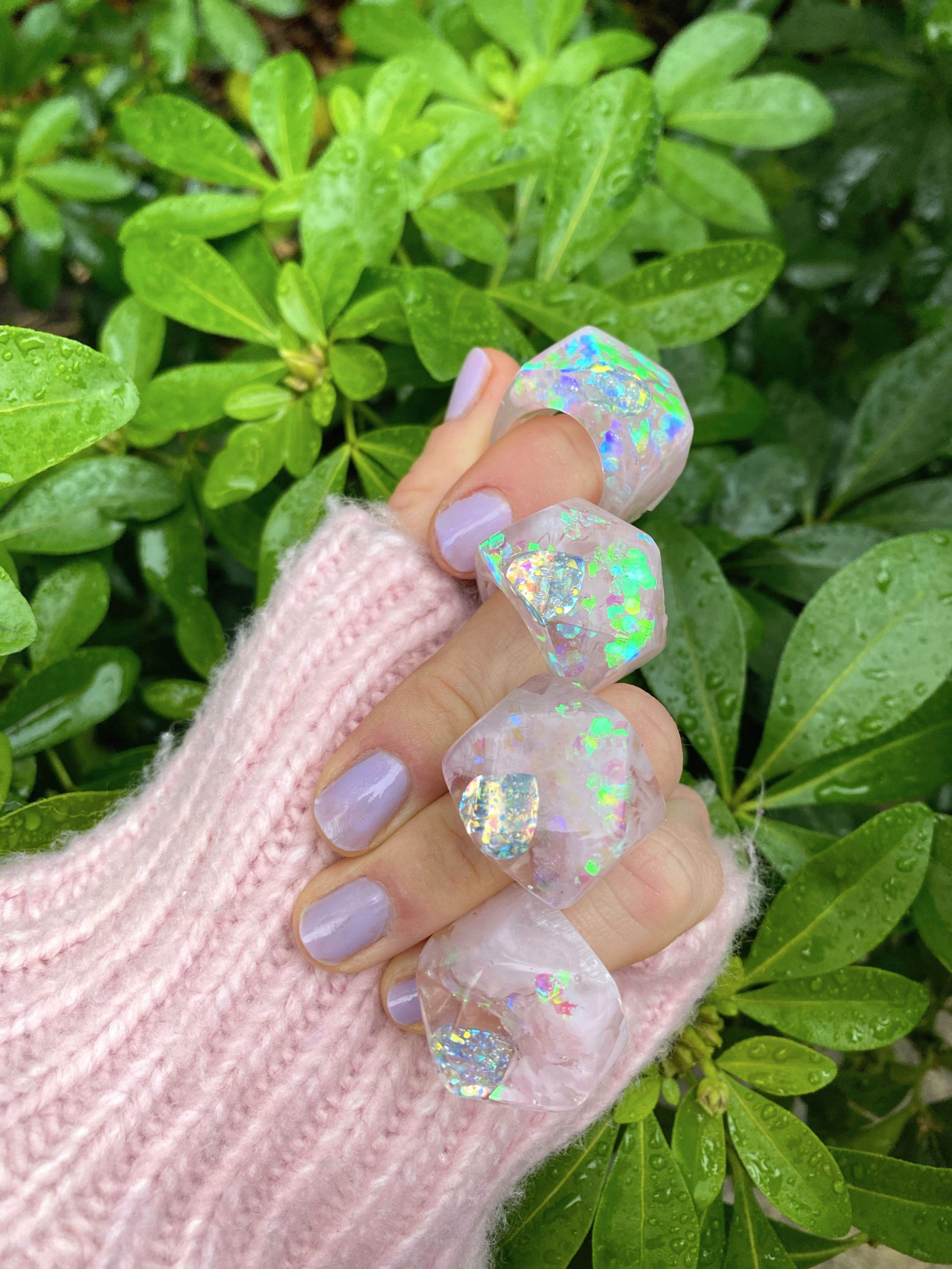 Iridescent heart rings worn on every finger of a hand in front of green bush